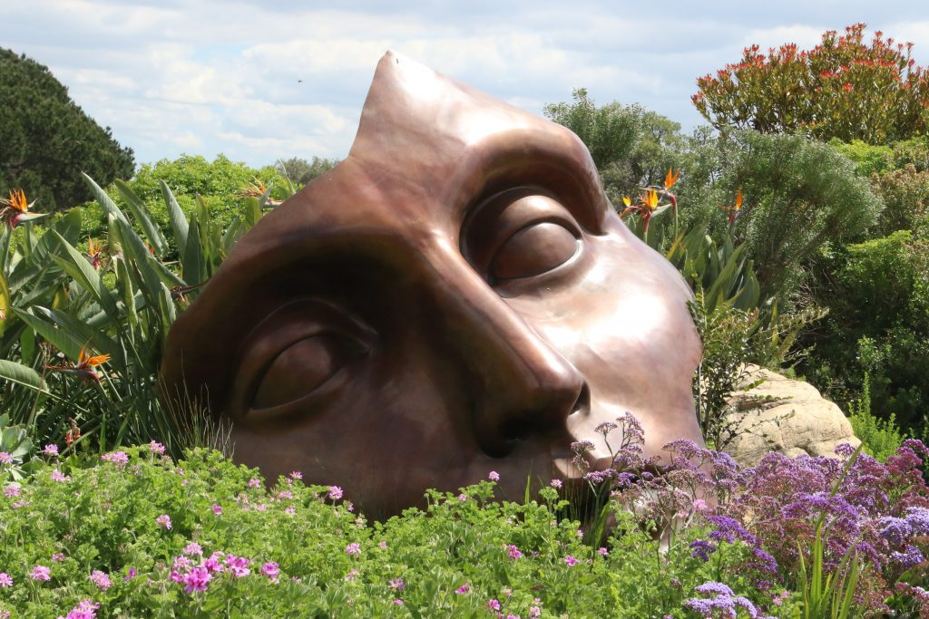 calm face sculpture in landscape